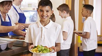 A young boy gets a plate including healthy fruits and vegetables from a school cafeteria
