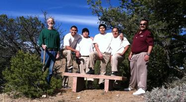 A group of men standing in front of a bench.