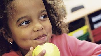 A young girl eats an apple in her school classroom.