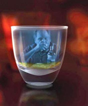 The image of a man drinking alcohol is reflected in a shot glass
