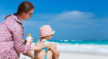 A mother applies sunscreen to her child's back to prevent over exposure to the sun at the beach.