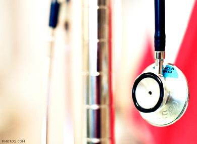 A stethoscope hangs on a wall of medical equipment