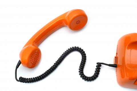 A red telephone handset connected to a red base by a black cord