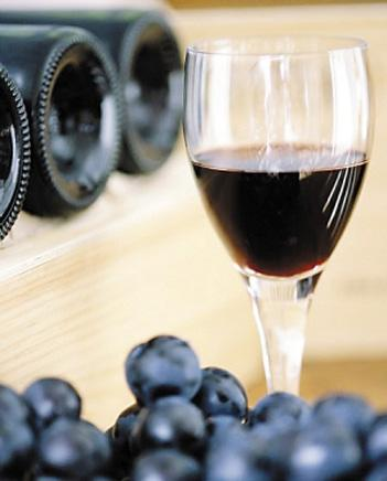A glass of wine sits near a group of grapes