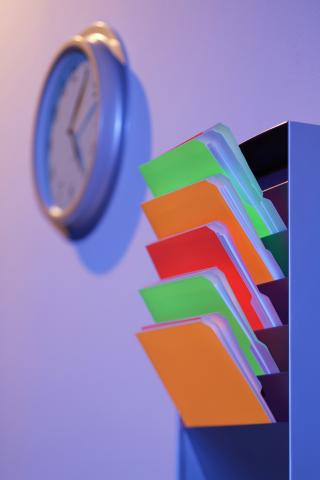 Color coded folders rest in a plastic wall mounted file divider