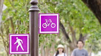 People walk along a trail marked for walkers and bicyclists.