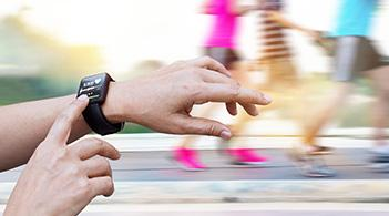 A runner checks his heart rate using a smartwatch.