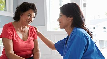 A promotora speaks to a female client about cervical cancer screening.
