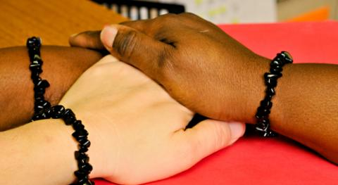 The hands of three women, one White and two African American, are stacked on top of each other; each wrist has a bracelet made from black coral.