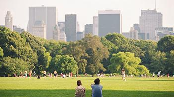 A couple sits in a park and watches others walk, run, and ride bikes.