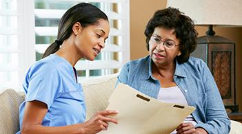 A community health worker reviews records with a patient.