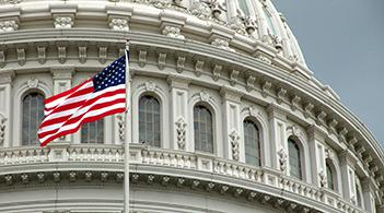 An American flag flying in front of the U.S. Capitol dome.