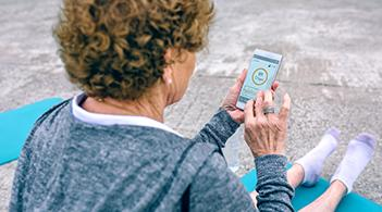 An older woman exercises with the help of a mobile phone.