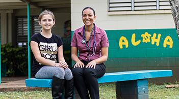 A student and school nurse sit side by side on a bench outside a school in Hawai`i.