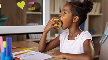 A young girl eats an apple while doing school work.