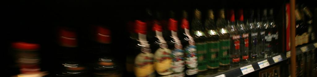 Bottles of alcohol on liquor store shelf representing Excessive Alcohol Consumption