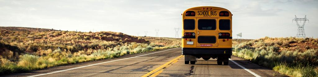 Back of a school bus seen driving away to represent School Closures for Emergency Preparedness