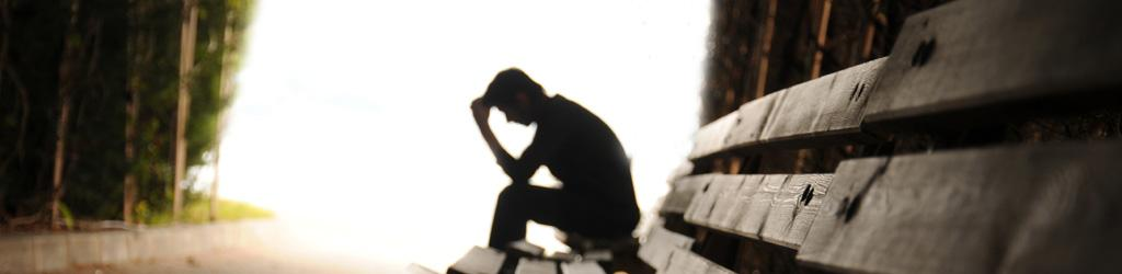 Silhouette of person on a bench with head in hands to represent Mental Health and Mental Illness