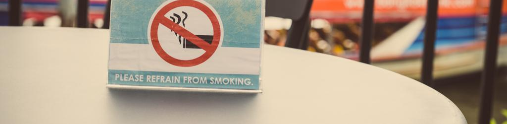 "Table tent reads ""Please refrain from smoking"" to represent Tobacco Use and Secondhand Smoke Exposure"