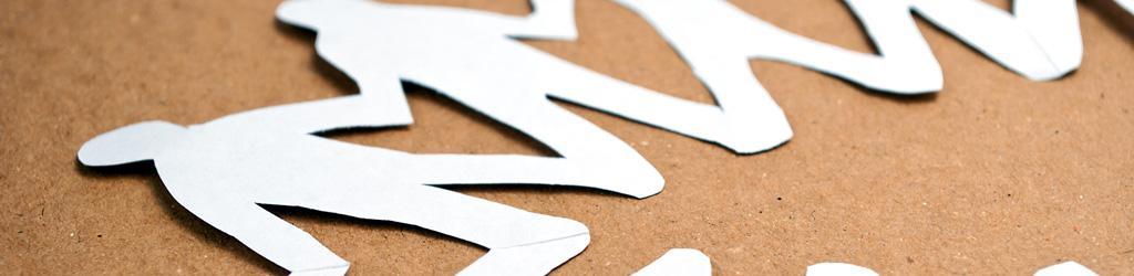 Paper doll cut-outs on a table to represent Violence Prevention in communities and schools