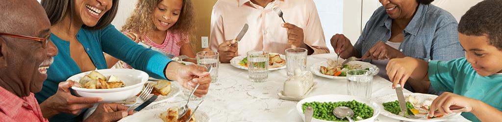 A family eats a healthy meal including vegetables, lean meat, and water